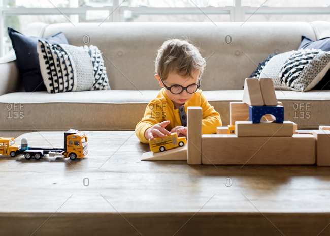 Young boy playing with toy cars and blocks