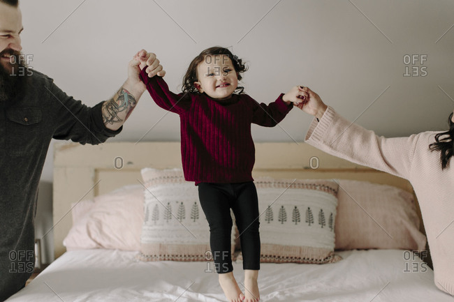 Parents playing with daughter bouncing on bed