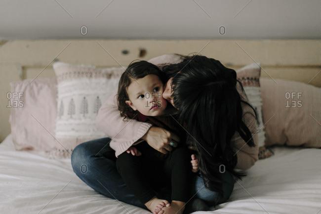 Mom kissing daughter on cheek in bedroom