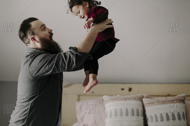 Father playfully lifting little girl in the air