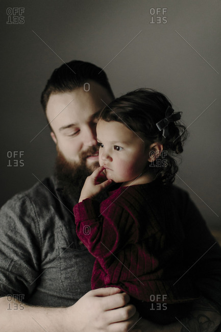 Dad holding young daughter