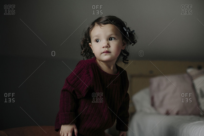 Little girl standing alone in room