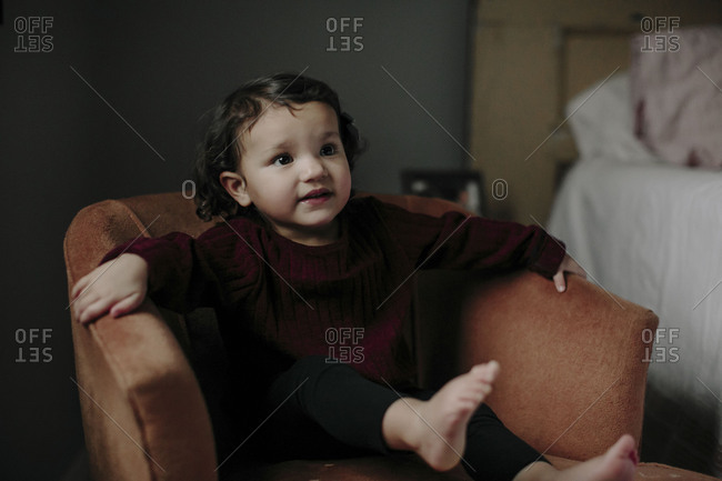 Portrait young girl sitting in armchair