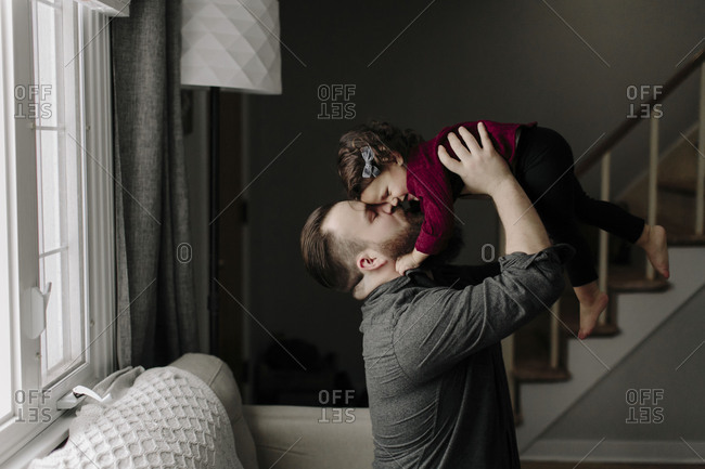 Father holding up daughter in living room
