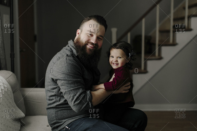 Daughter and dad sitting together in living room