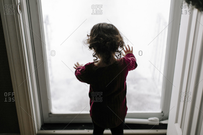 Little girl looking out glass door