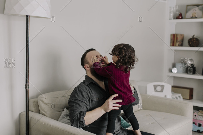 Little girl playfully grabbing dad's face