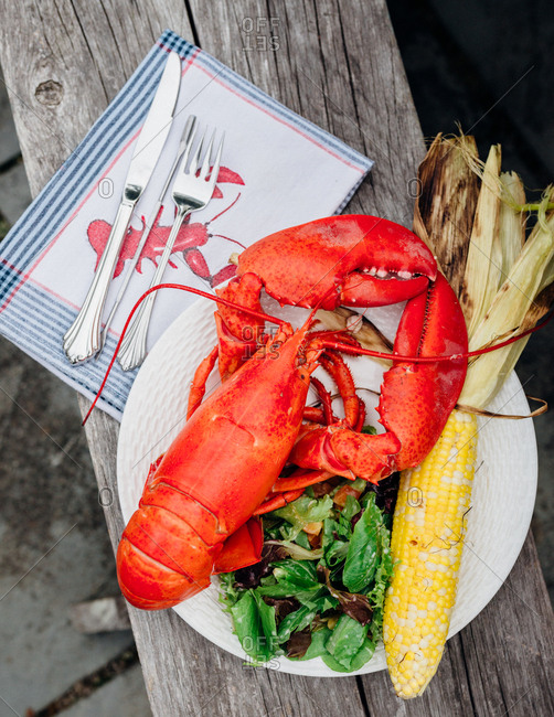 Lobster served with corn on the cob and salad
