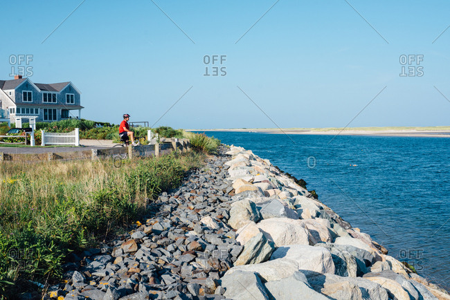 Cape Cod, Massachusetts, USA - September 4, 2017: Bicyclist stopping to look at scenic view of bay