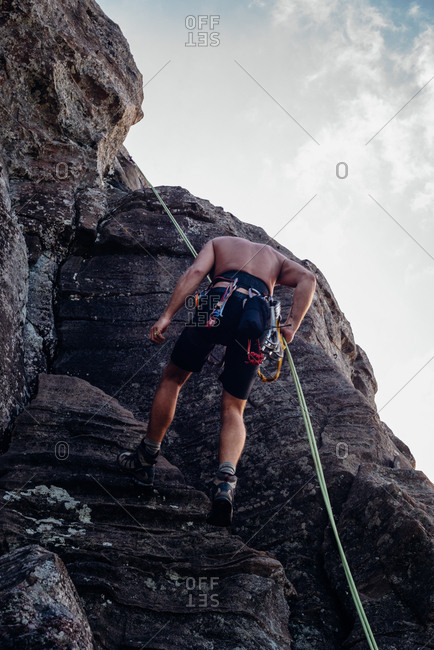 Rock climber using ropes to descend rock face