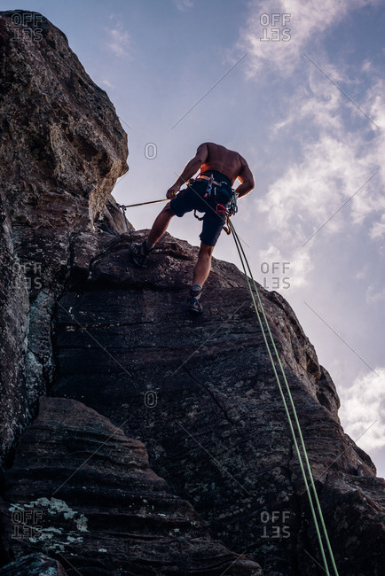 Rock climber using ropes to ascend rock face