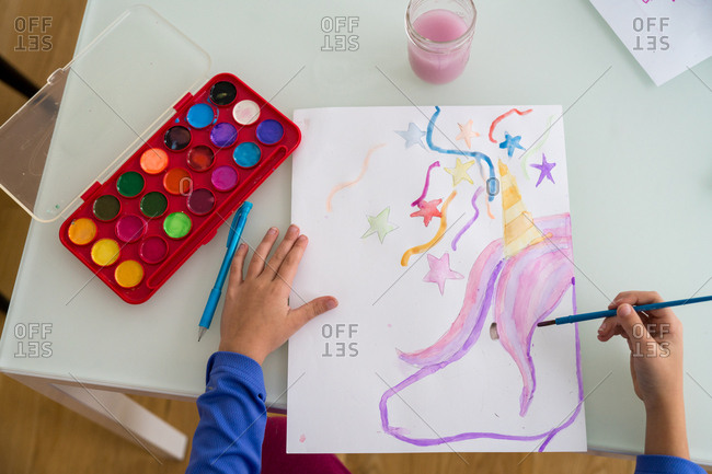 Overhead view of young girl painting a colorful Unicorn