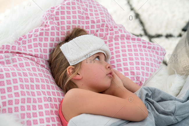 Overhead view of sick young girl lying on couch with washcloth on head
