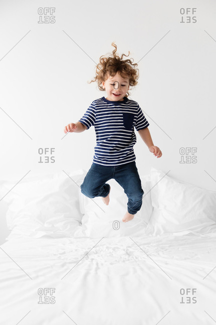 Little boy bouncing on bed