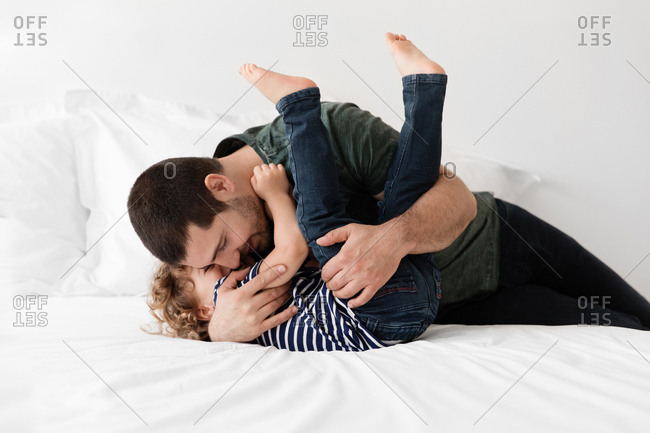 Young dad wrestles with little son on bed