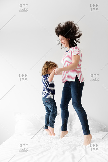 Mother and young son jumping up and down on bed together