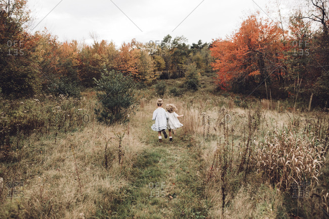 Girls running through overgrown field together