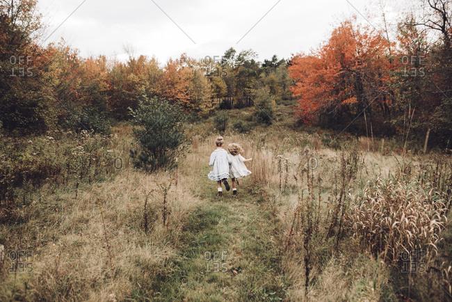 Girls running through overgrown field together