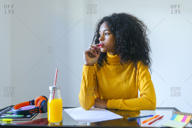 Young woman looking towards the window while studying