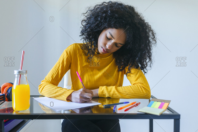 Young woman taking notes with pen and paper