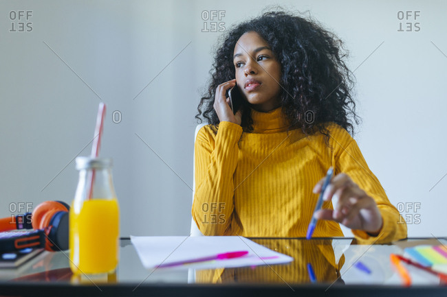 Young woman talking on the phone at her desk