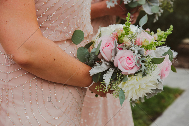 Bridesmaid holding bouquet of roses and dahlias