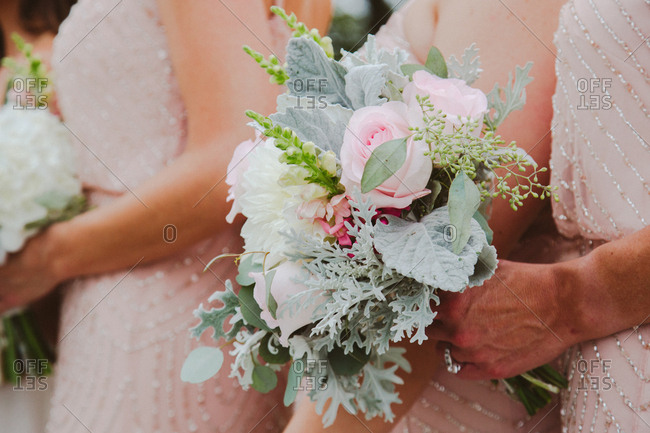 Close up of bridesmaids holding bouquet of roses and dahlias