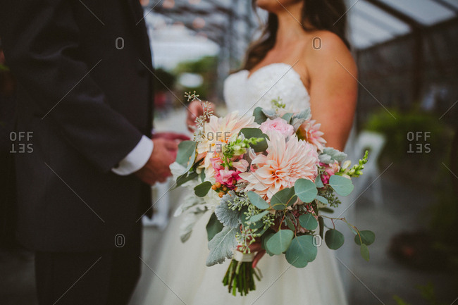 Bride and groom with focus on bouquet