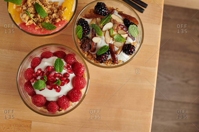 Cropped overhead view of three breakfast parfait bowls