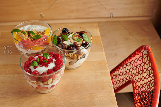 Dining table with three servings breakfast fruit and yogurt parfaits