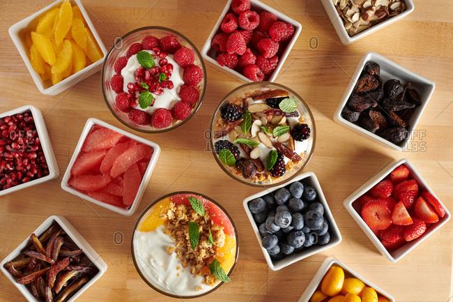 Breakfast yogurt parfaits with spread of various toppings