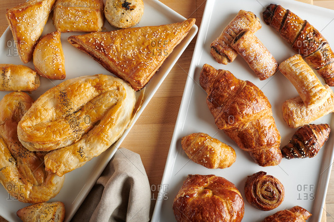 Array of multicultural pastries, breads, and croissants on rustic linen
