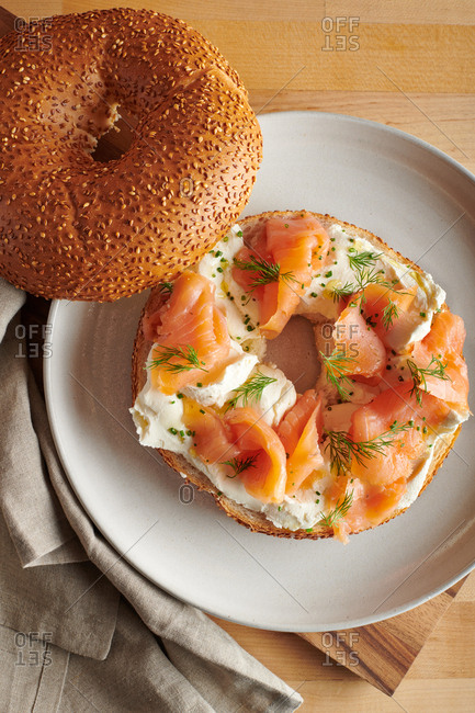 Sesame cream cheese bagel and lox garnished with dill on dinner plate