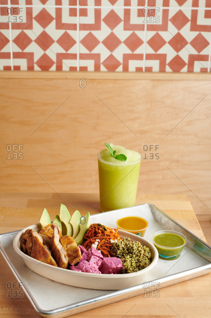 Fast casual Middle eastern lunch with chicken and quinoa with a glass of fresh fruit smoothie