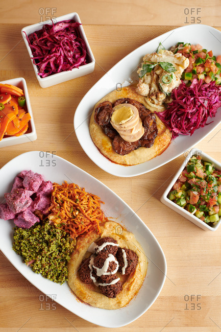Top view of Middle eastern style hummus entrees with miscellaneous sides