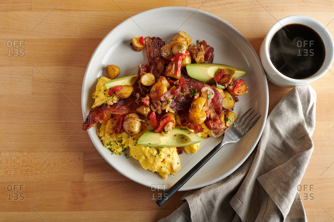 Overhead view of scrambled egg breakfast with potatoes and bacon with cup of fresh coffee