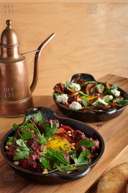 Two fresh shokshoukas prepared in cast iron skillets with rustic copper pot