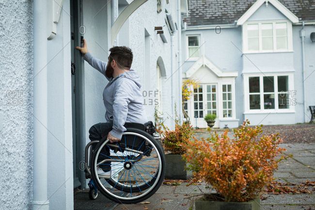 Disabled man ringing the door bell of his home