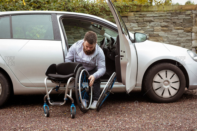 Disabled young man holding wheelchair while getting out of a car