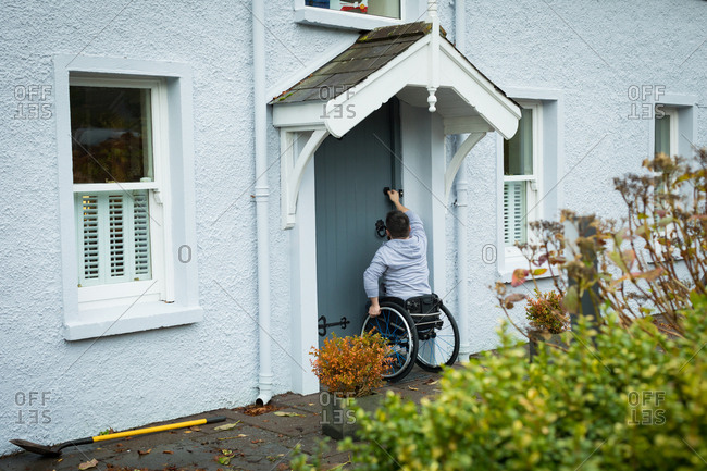 Disabled man opening the door of his home