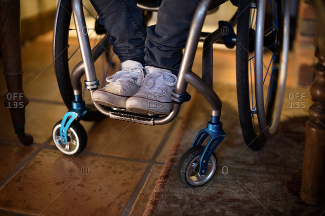Low section of disabled man in wheelchair at home