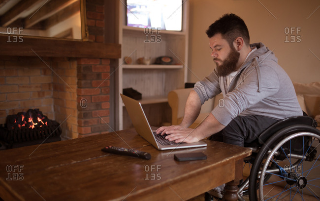 Disabled young man using laptop at home
