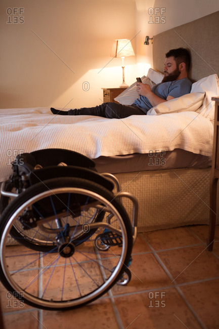 Disabled man using mobile phone in bedroom at home