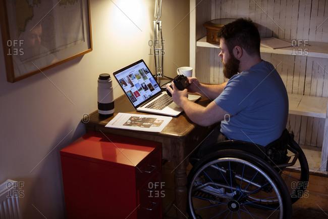 Disabled man looking at photos in camera at home
