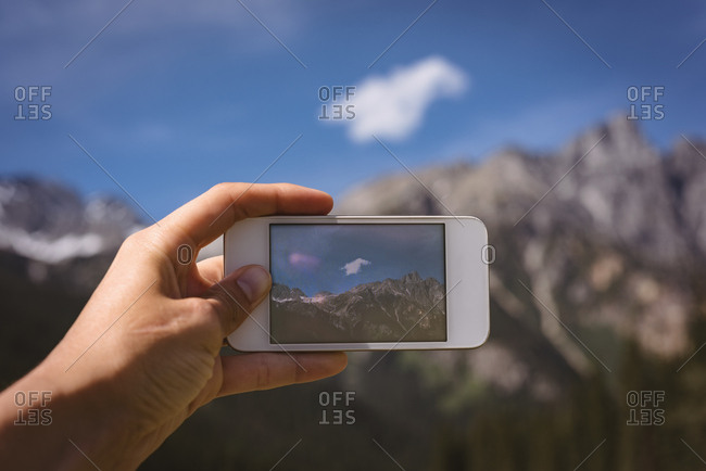 Close-up of man taking photo of mountains with mobile phone
