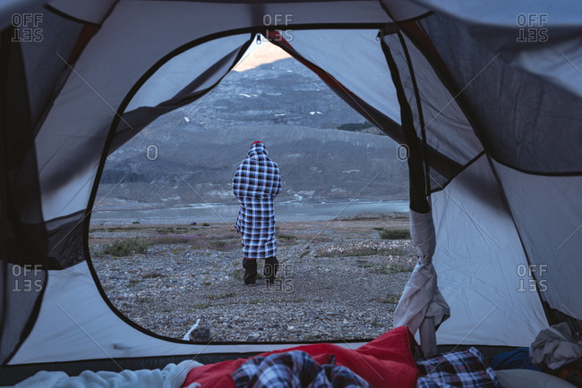 Rear view of man wrapped up in blanket near tent