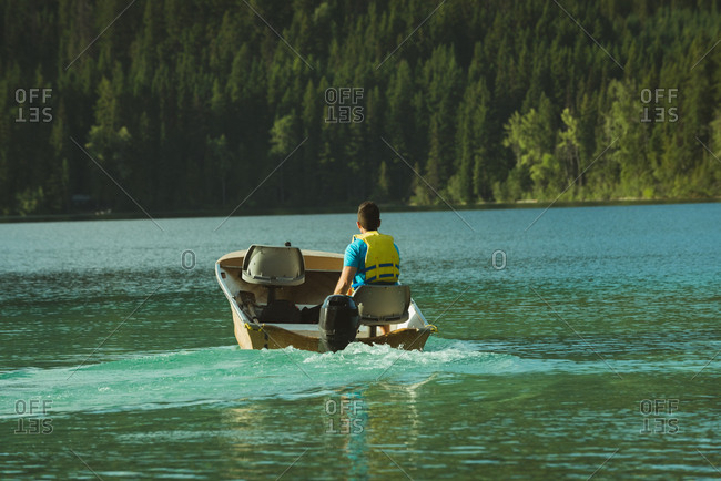 Rear view of man travelling in motorboat on a lake