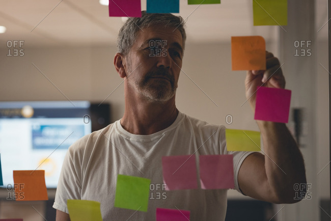 Businessman writing on sticky notes in office