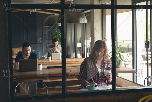 Businesswoman writing on a diary in cafeteria at office