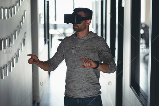 Businessman using virtual reality headset in corridor at office